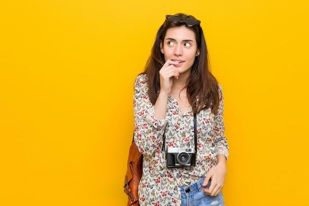 Femme jeune voyageur brune détendue pensant à quelque chose en regardant un espace de copie.