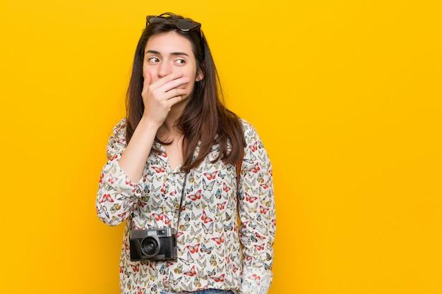 Femme jeune voyageur brune réfléchie à la recherche d'un espace copie couvrant la bouche avec la main.