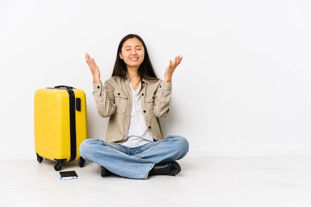 Femme jeune voyageur chinois assis tenant une carte d'embarquement criant vers le ciel, levant les yeux, frustré.