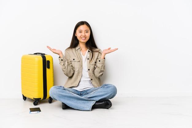 Femme jeune voyageur chinois assis tenant une carte d'embarquement fait échelle avec les bras, se sent heureux et confiant.