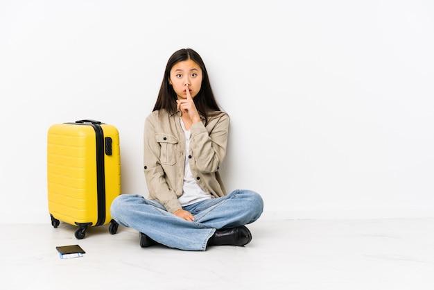 Femme jeune voyageur chinois assis tenant une carte d'embarquement en gardant un secret ou en demandant le silence.