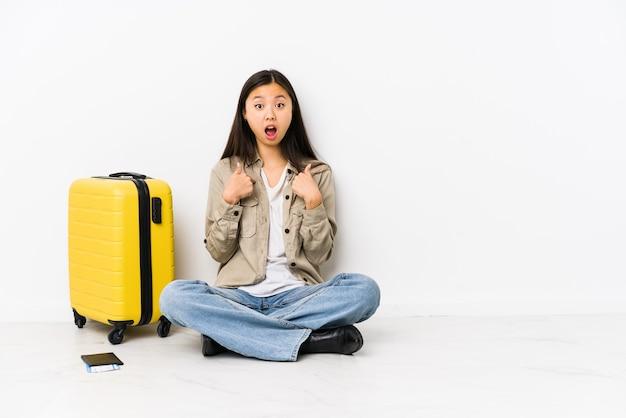 Femme jeune voyageur chinois assis tenant une carte d'embarquement surpris pointant avec le doigt, souriant largement.