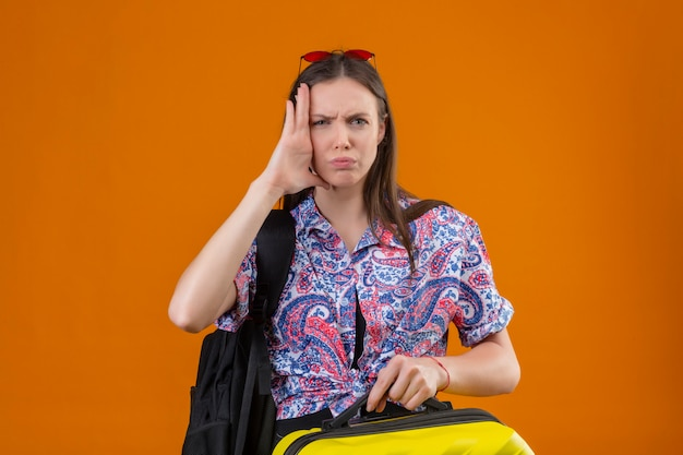 Femme jeune voyageur dérangé portant des lunettes de soleil rouges sur la tête debout avec sac à dos tenant la valise à la tête de contact stressée et ennuyée avec la main sur l'orange