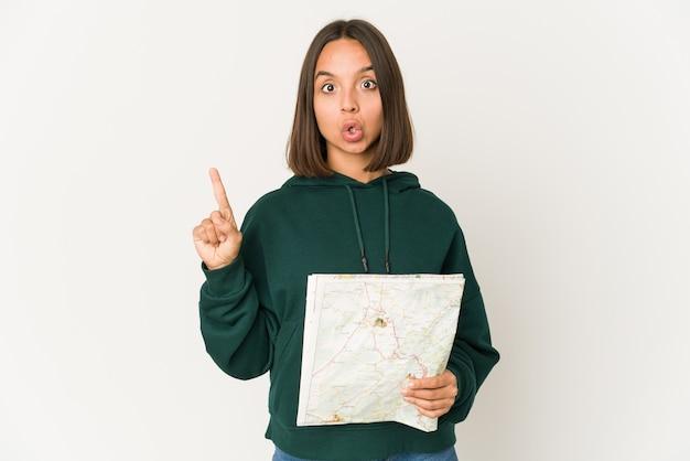 Femme jeune voyageur hispanique tenant une carte ayant une excellente idée, concept de créativité.