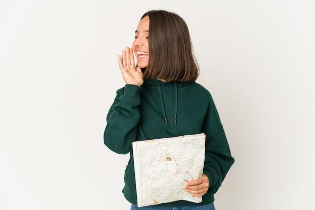 Femme jeune voyageur hispanique tenant une carte criant et tenant la paume près de la bouche ouverte.