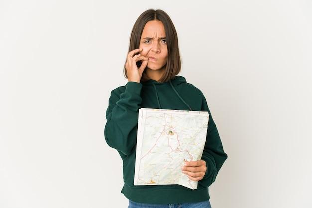 Femme jeune voyageur hispanique tenant une carte avec les doigts sur les lèvres en gardant un secret.