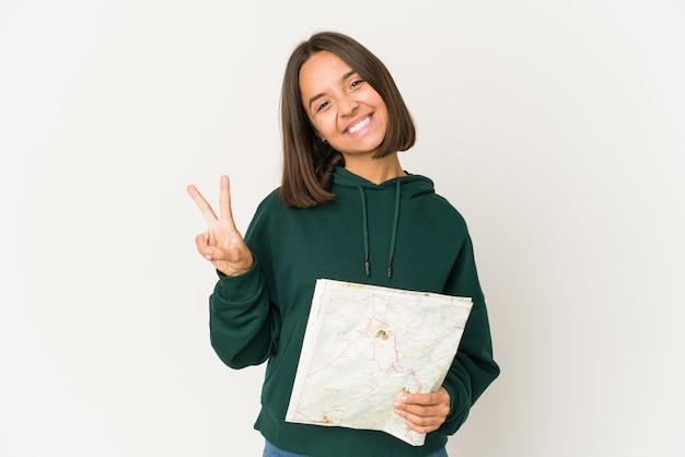 Femme jeune voyageur hispanique tenant une carte montrant le numéro deux avec les doigts.