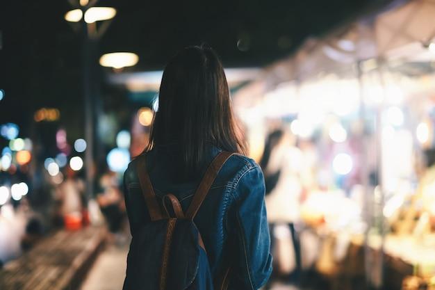 Femme jeune voyageur marchant dans la rue pendant la nuit.