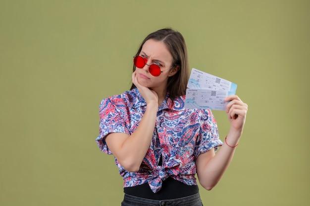 Femme jeune voyageur portant des lunettes de soleil rouges tenant des billets debout avec la main sur le menton mécontent et pensant avec une expression pensive sur fond vert