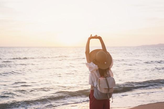 Femme jeune voyageur se détendre sur une plage tropicale au coucher du soleil