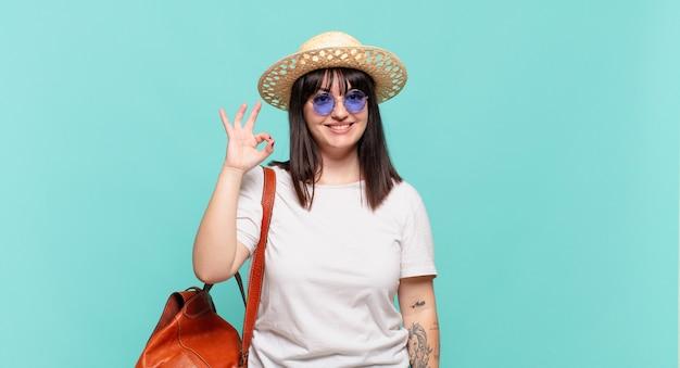 Femme jeune voyageur se sentir heureux, détendu et satisfait, montrant son approbation avec un geste correct, souriant