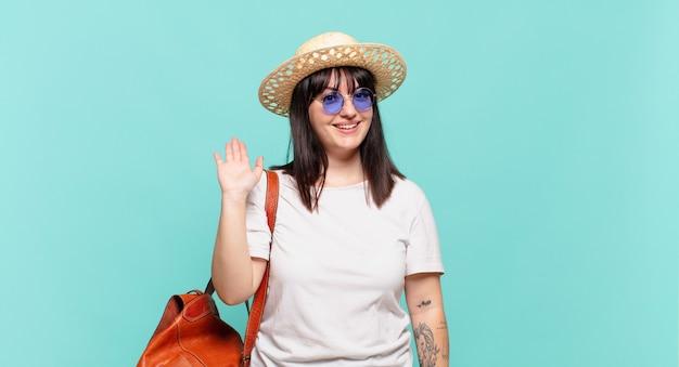 Femme jeune voyageur souriant joyeusement et gaiement, en agitant la main, en vous accueillant et en vous saluant, ou en vous disant au revoir