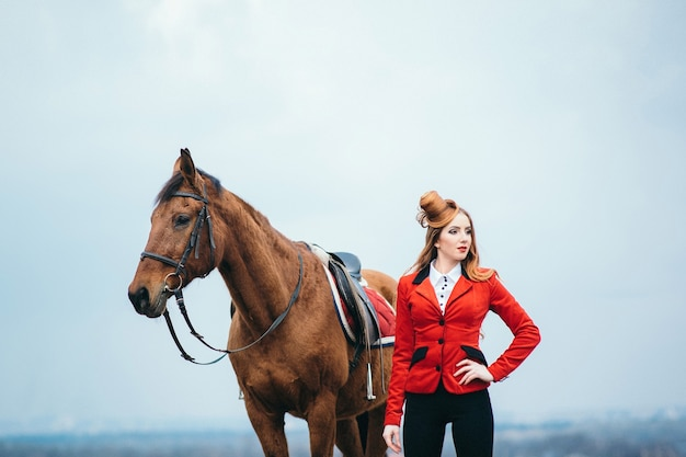 Femme jockey aux cheveux roux dans un cardigan rouge et des bottes noires avec un cheval pour une promenade
