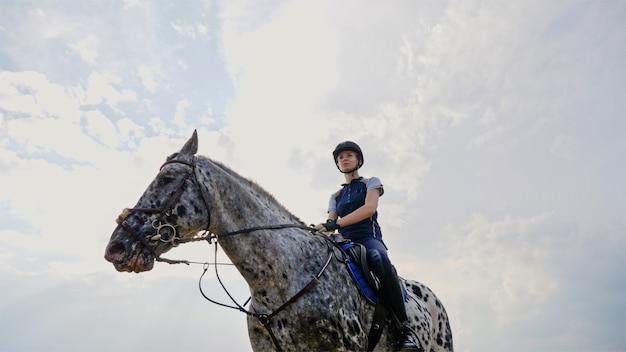 Femme jockey monté sur un cheval.