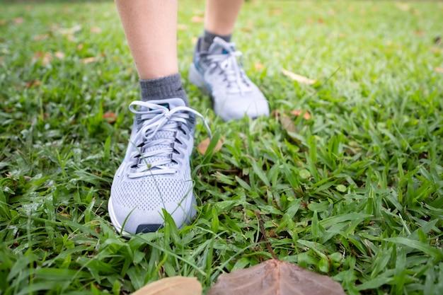 Femme jogging à central park en portant des chaussures de sport exercice au coucher du soleil