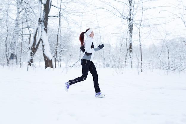 Femme jogging dans les bois d'hiver