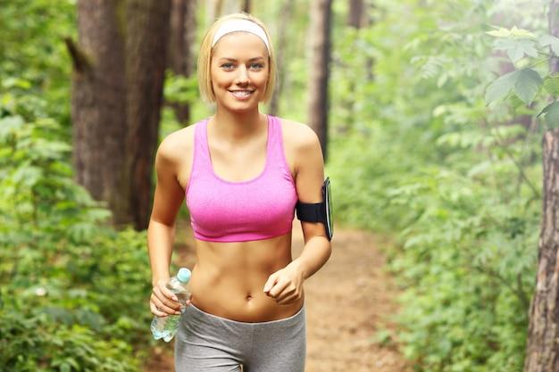 Femme jogging dans la forêt avec une bouteille d'eau