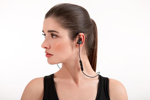 Femme en jogging haut noir écouter de la musique sur des écouteurs posant isolé sur blanc