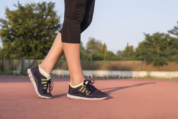 Femme de jogging portant des baskets noires et un pantalon noir