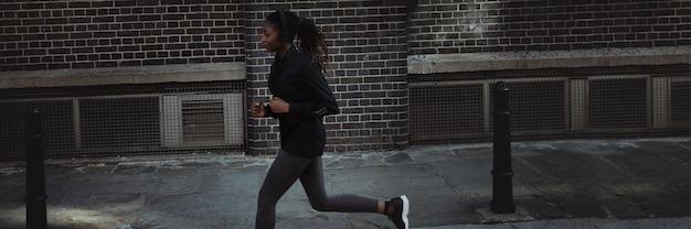 Femme jogging à travers la ville