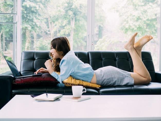 Femme jolie asiatique internet travaille en ligne à la maison et se détendre style de vie avec son labtop