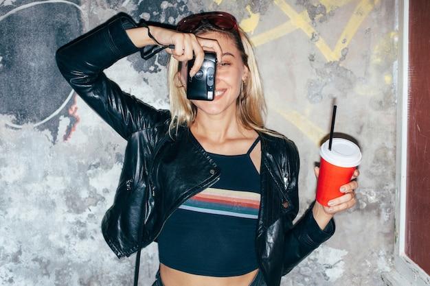 Femme jolie blonde posant en été, boire du café en faisant des photos avec un ancien appareil photo argentique