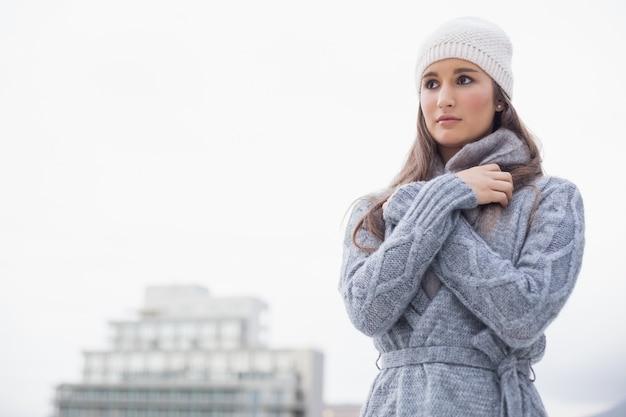 Femme jolie froide avec des vêtements d'hiver sur posant