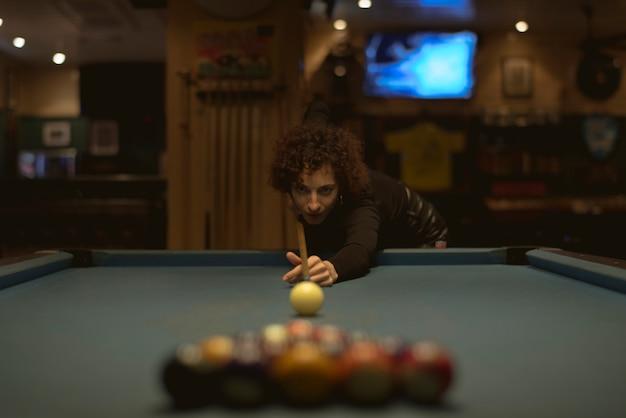 Femme jouant au billard dans un bar