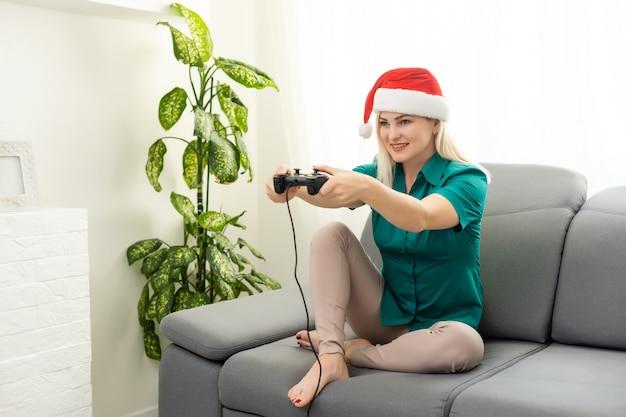 Femme jouant au jeu vidéo sur le canapé dans la chambre, nouvel an et noël