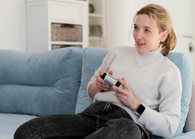 Femme jouant au jeu vidéo à la maison