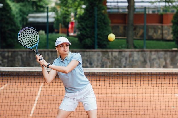Femme jouant au tennis et attendant le service.