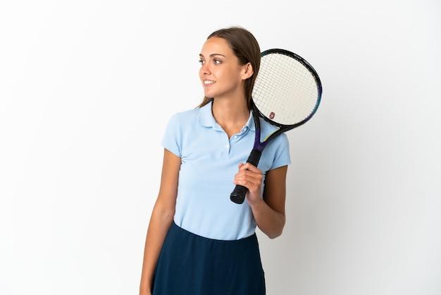 Femme jouant au tennis sur un mur blanc isolé à côté