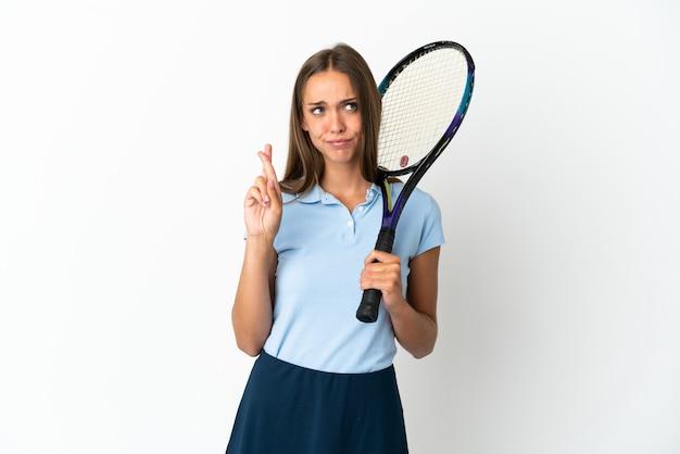 Femme jouant au tennis sur un mur blanc isolé avec les doigts croisés et souhaitant le meilleur