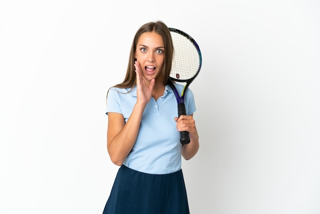 Femme jouant au tennis sur un mur blanc isolé avec une expression faciale surprise et choquée