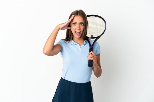 Femme jouant au tennis sur un mur blanc isolé avec une expression surprise