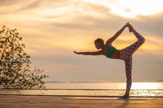 Femme jouant au yoga sur la terrasse de la plage de la mer contre beau ciel coucher de soleil