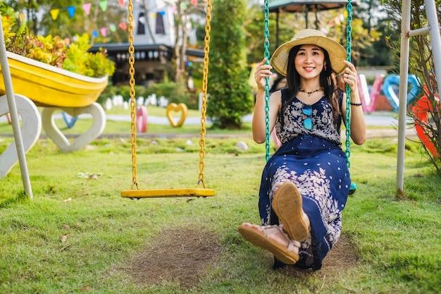 Une femme jouant une balançoire dans la cour de récréation