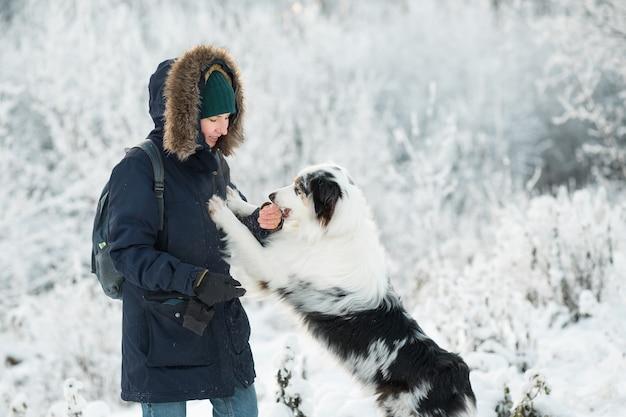 Femme jouant avec un berger australien dans la forêt d'hiver.