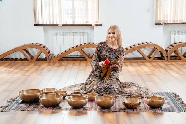 Femme jouant sur un bol chantant tibétain pour la thérapie sonore