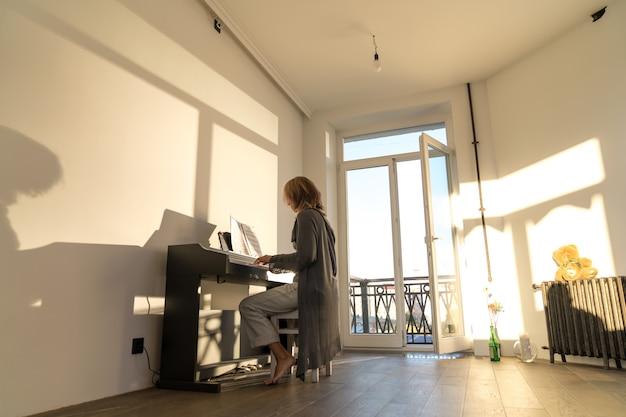 Femme jouant du piano électronique dans son appartement