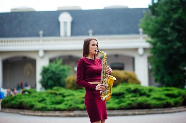 Femme jouant du saxophone dans les rues de la ville