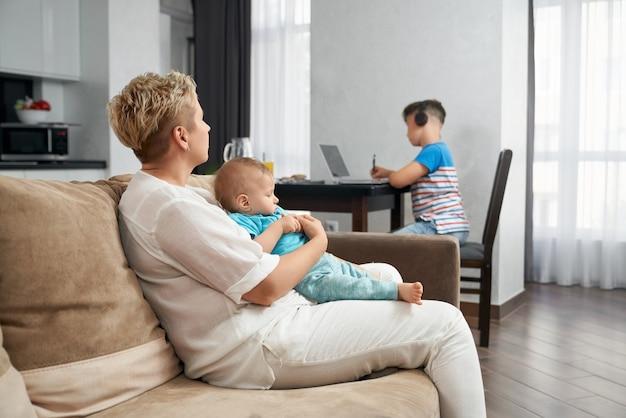 Femme jouant avec enfant en bas âge tout en fils aîné à l'aide d'un ordinateur portable