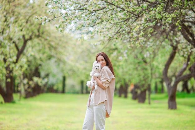 Femme jouant et étreignant un chiot dans le parc