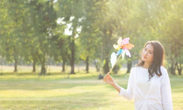 Femme jouant avec des fleurs dans un parc public