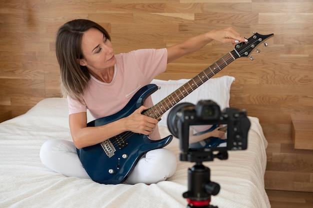 Femme jouant de la guitare électrique à la maison