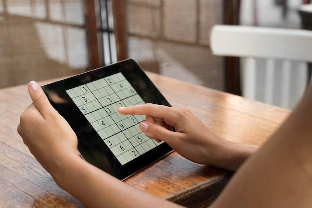 Femme jouant à un jeu de sudoku sur sa tablette