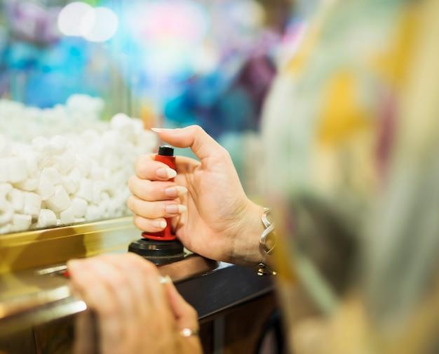 Femme jouant avec une machine à griffes