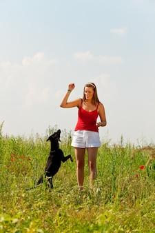 Femme jouant avec son chien dans un pré