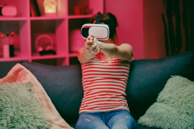 Femme jouant et souriant dans le casque vr. casque de réalité virtuelle sur éclairage couleur