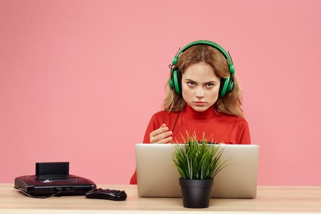 Une femme joue à un jeu d'ordinateur dans des consoles avec des joysticks dans les écouteurs avec un ordinateur portable
